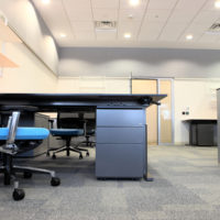 Empty office with new modern office furniture including desks cupboards filing cabinets and chairs. Two blue chairs facing out. HDR type image